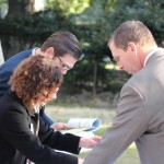 Outside the tent, CSBA's Nathaniel Browning and an ACSA staffer offer board members materials for the State Board meeting.