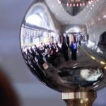 The reflection in the pendulum in the lobby of the CDE shows a crowd waiting to comment.